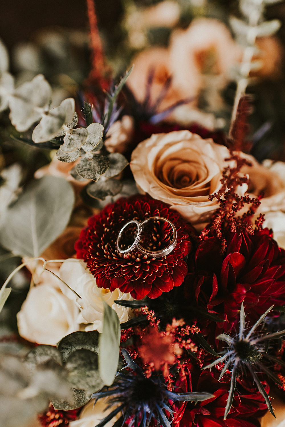 wedding rings in a bouquet with red and white flowers