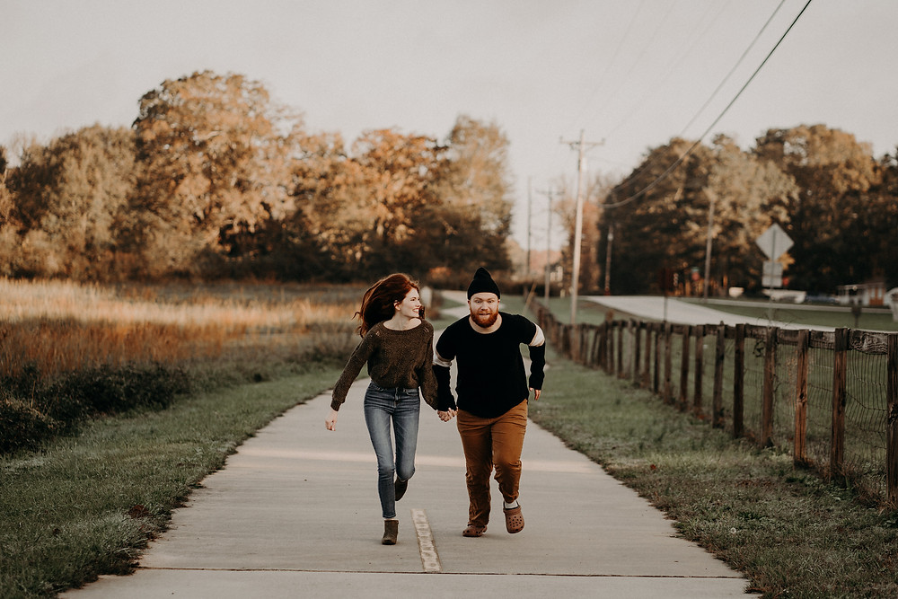 red-haired couple running holding hands