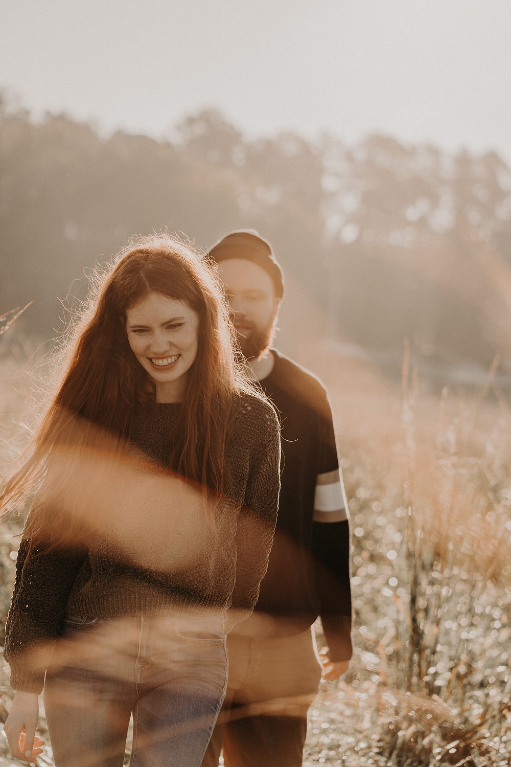 Film inspired moody engagement photography. Atlanta wedding photographer. Young ginger couple in fall clothes in a field with sunlight
