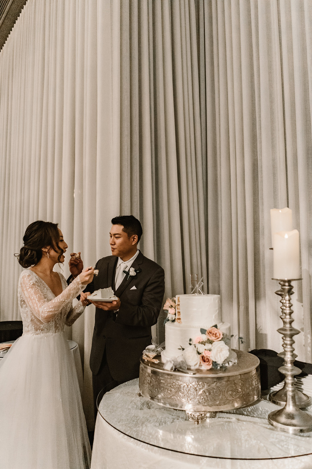 asian bride and groom eating their wedding cake