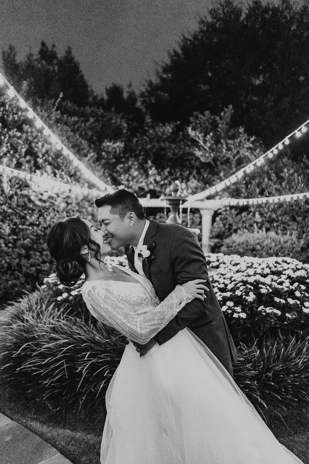 Black and white photo of asian bride and groom dancing in a garden at night