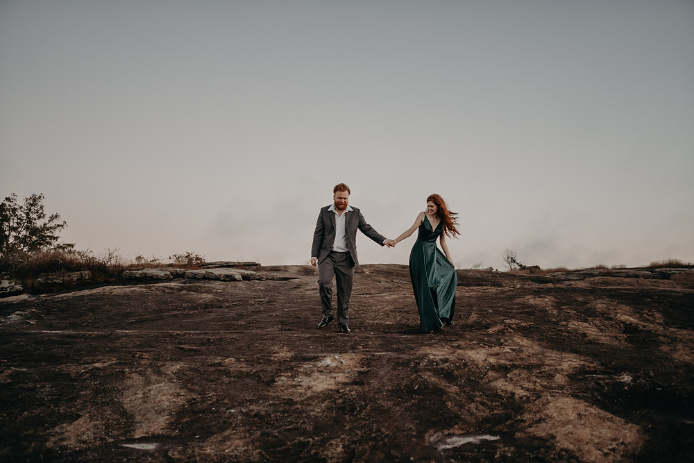 red-haired couple wearing formal clothes walking hand in hand on arabia mountain