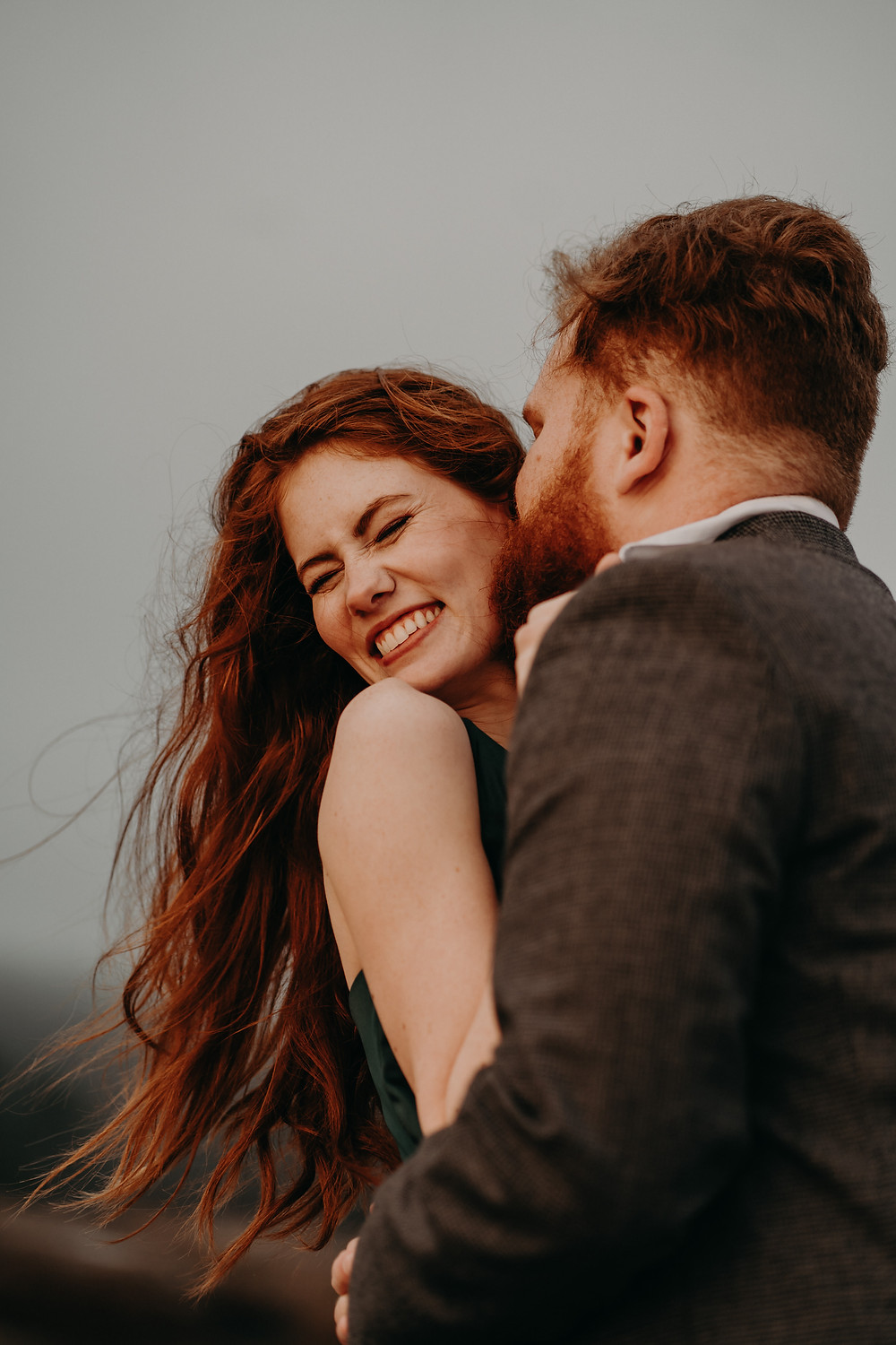 red-haired couple wearing formal clothes for their engagement session at arabia mountain