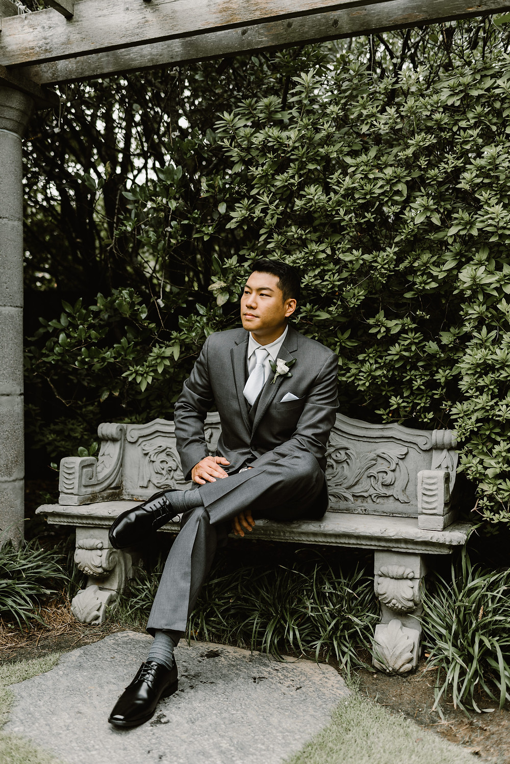 Asian groom wearing a gray suit in a garden