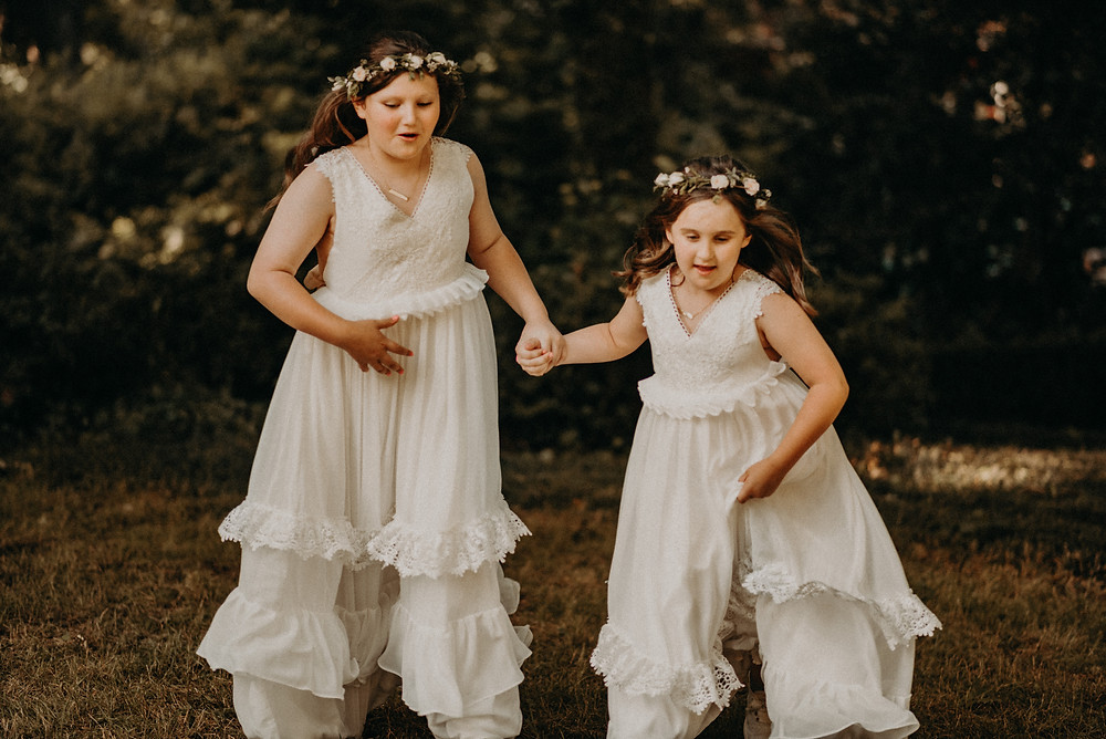 2 little flower girls holding hands at Cherry Hollow Farm, GA