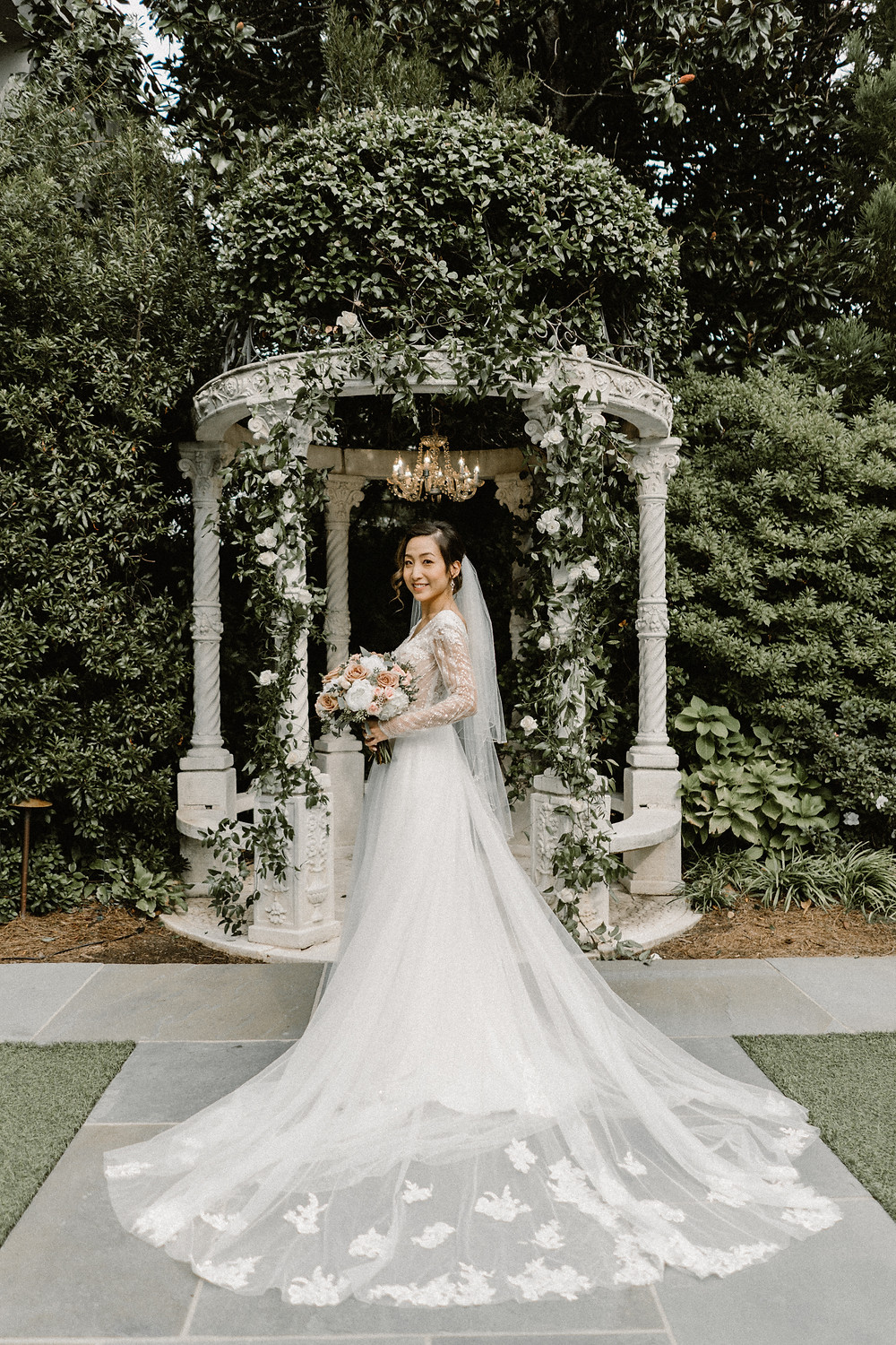 Asian Bride wearing a long sleeved tulle wedding dress in a garden
