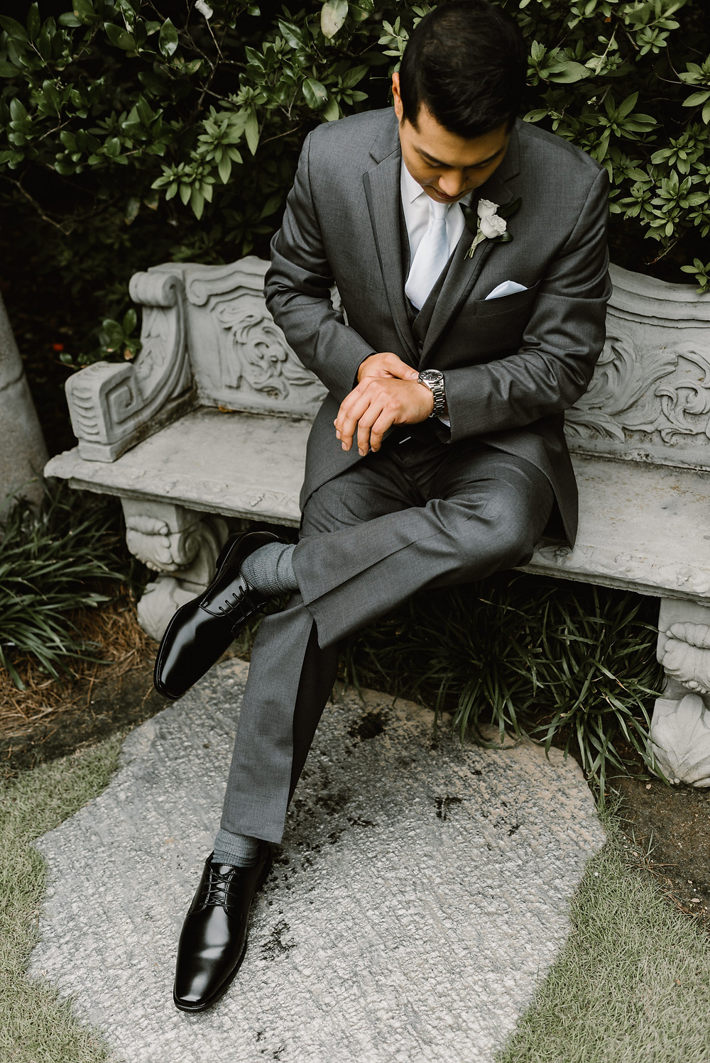 Asian Groom in a gray suit looking at his watch