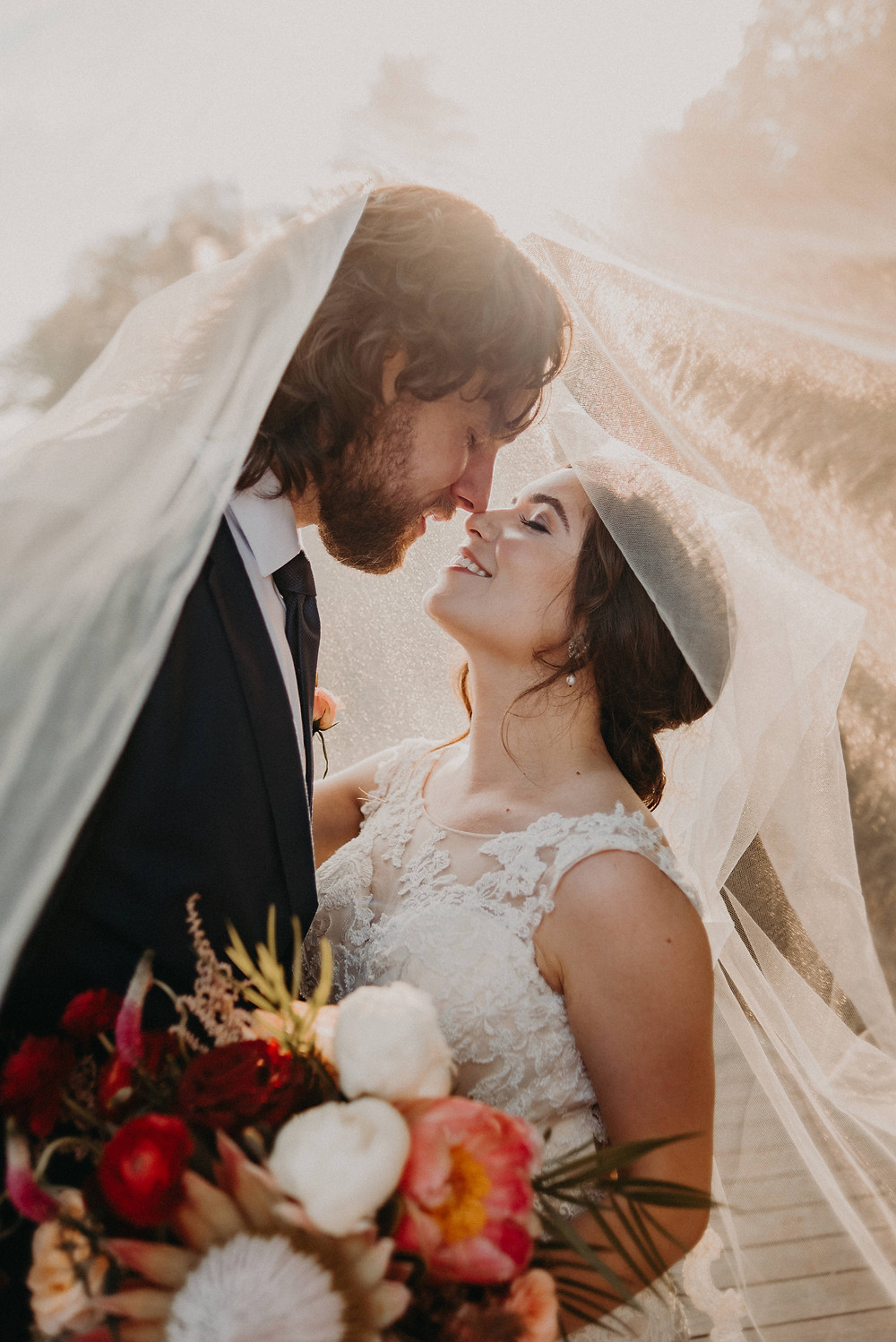 Bride and Groom under the veil with a colorful bouquet