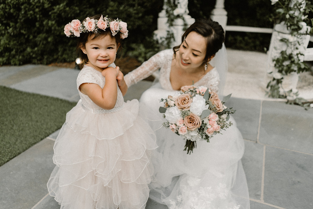 Bride with her flower girl wearing white tulle dresses with rose flowers