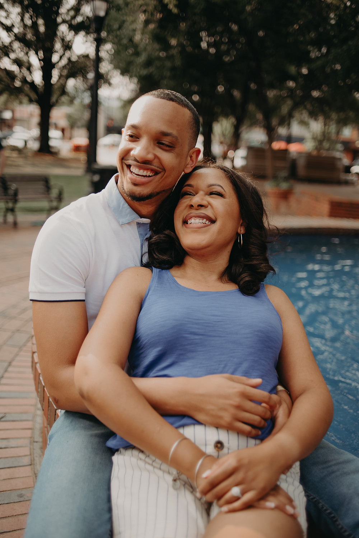 Couple smiling in engagement session. Marietta Square, GA