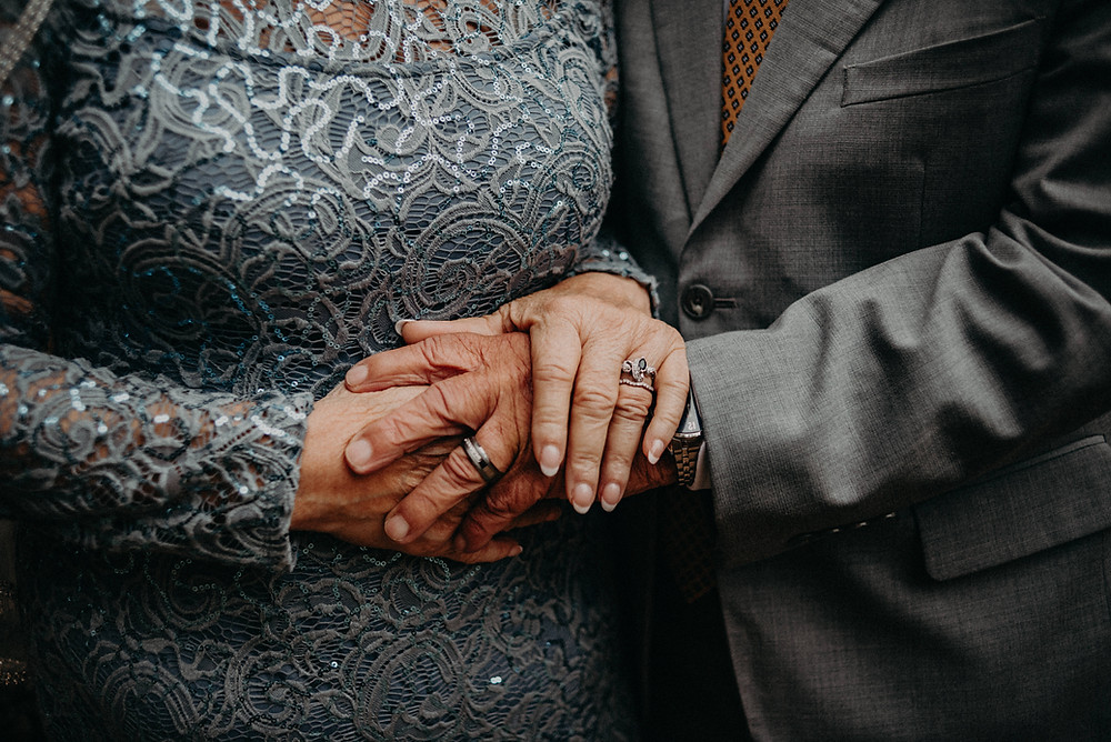 Elderly couple holding hands at their wedding