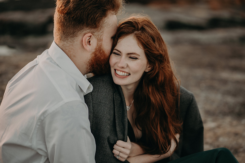 Moody engagement photography. Ginger bride smiling hugging her fiance at the mountain