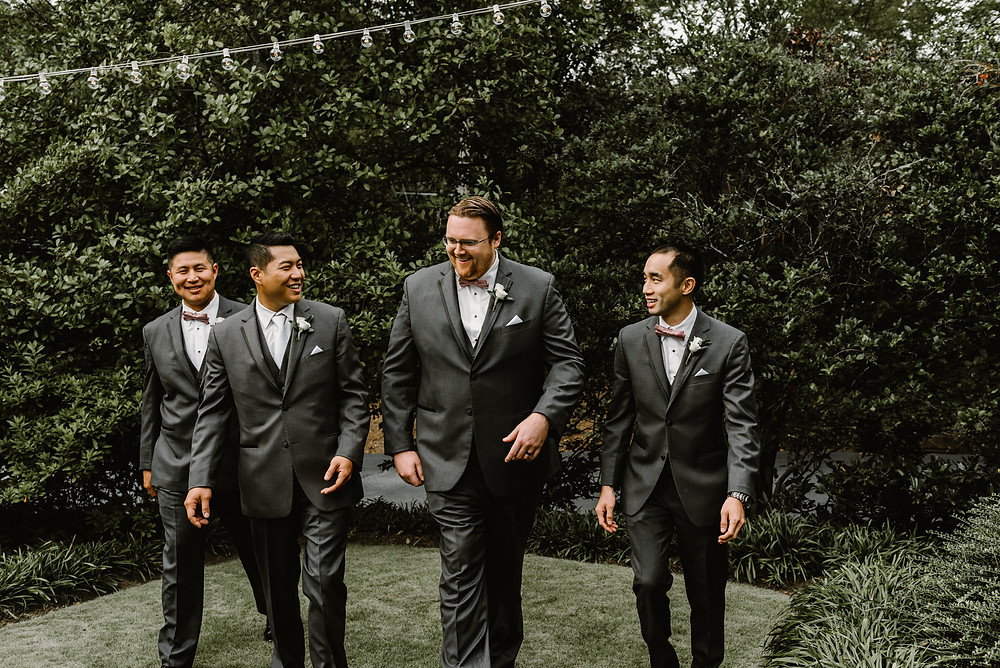 Groom and groonsmen walking in a garden wearing gray suits