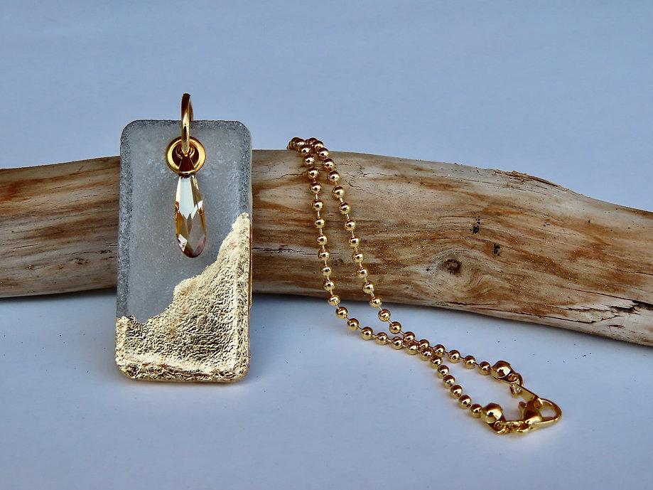 collier artisanal à pendentif rectangulaire en ciment feuille d'or 24K et goutte en cristal Swarovski, posé sur un bois flotté