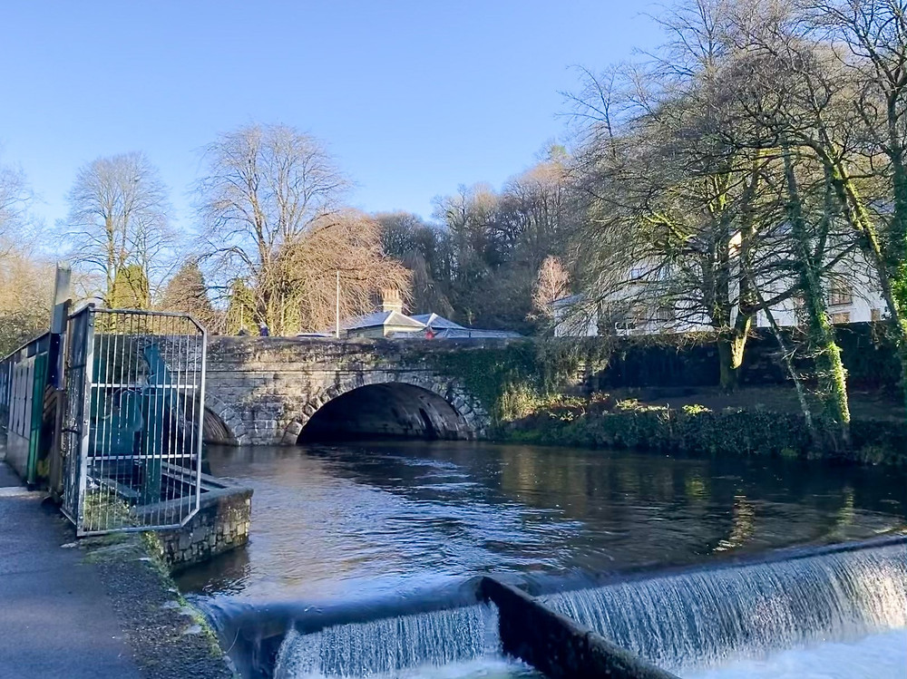 A long shot image of Abbey Bridge over the River Tavy in Tavistock. The weir is to the left.