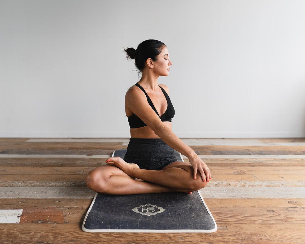 Femme sur tapis de yoga assise