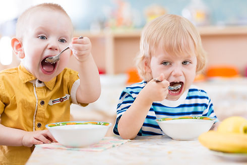 Funny little kids eating from plates in