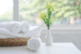 Roll up of white towels on basket on whi