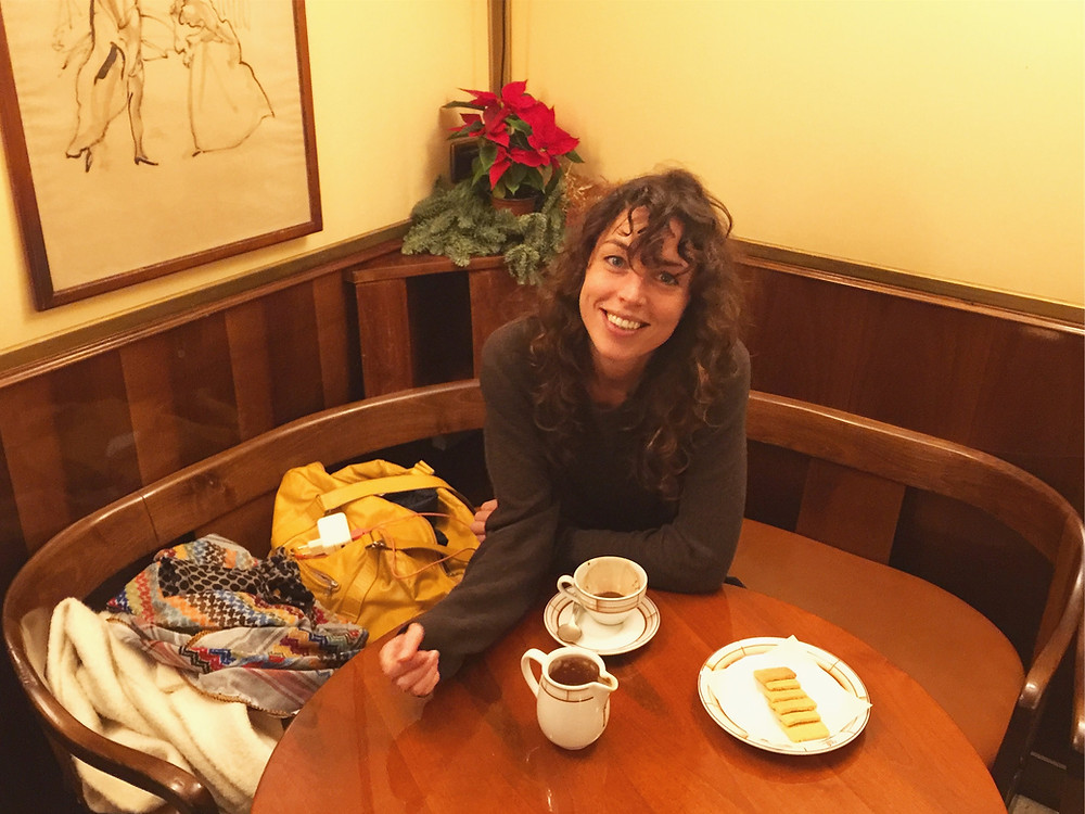 Natalie Vansier sitting at a corner table in an old restaurant, drinking a hot chocolate with a small plate of cookies next to her.