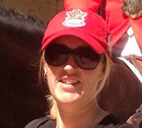 Close-up of Megan Armit smiling wearing a Canada baseball hat and sunglasses