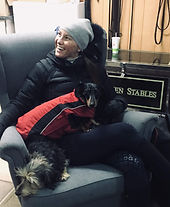 Whitney Sorensen laughing with her two dogs on her lap with a Sorensen Stables equipment trunk behind her