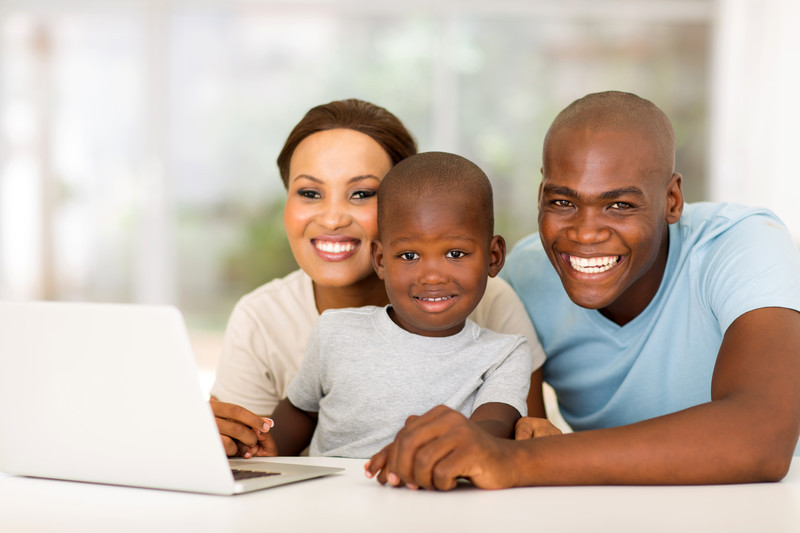 Family with young child on the computer.