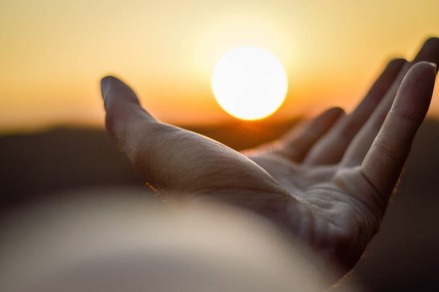 An open hand reaching for the Sun. - A New Beginning