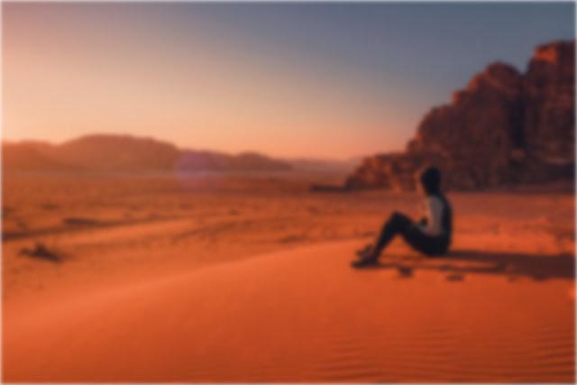 A Person Sitting on A Sandy Plain