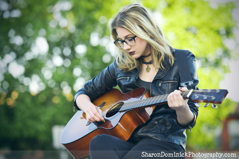 Beautiful teen girl playing acoustic guitar outdoors