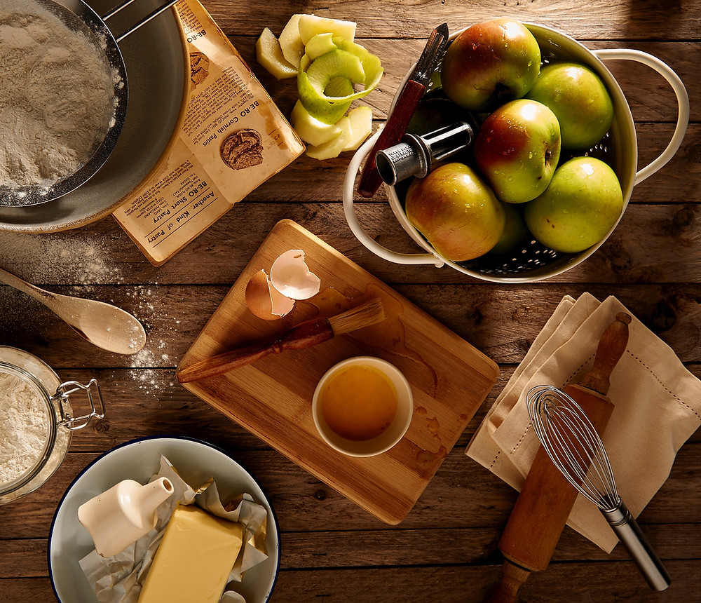 A colander of apples, a bowl of flour, a wooden spoon, a wooden board with some beaten egg.