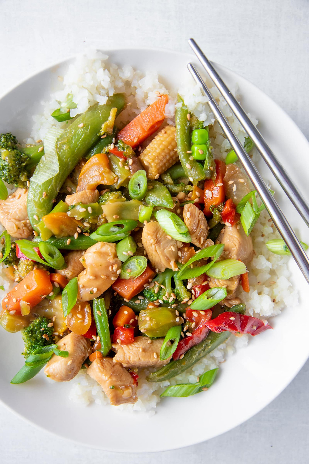 chicken stir fry on a plate with chopsticks