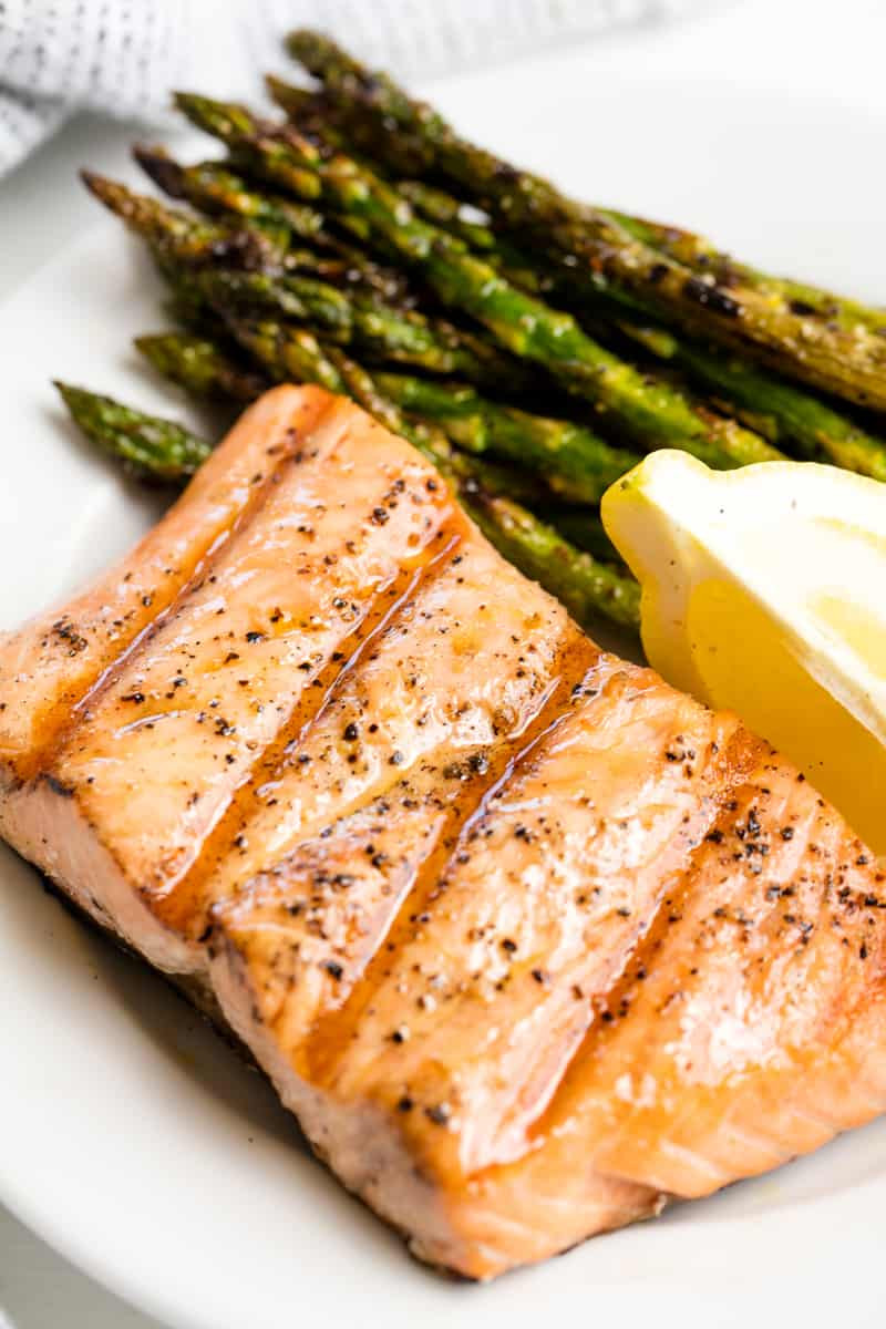 grilled salmon with asparagus and a lemon wedge on a plate