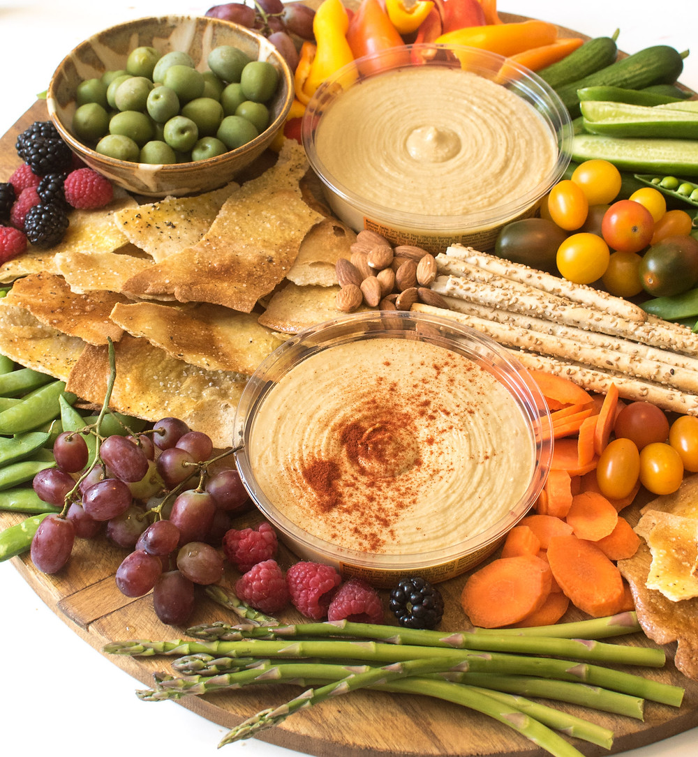 a platter of homemade hummus with vegetables for dipping