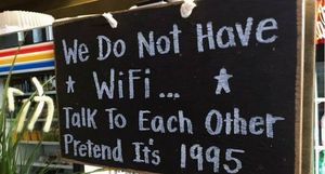 a funny sign outside of a restaurant that states they do not have WiFi, which means we have to talk to each other