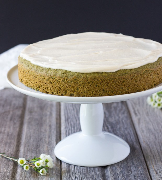 vegan matcha cake with frosting on a pedestal