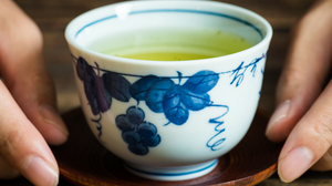 green tea in a cup being held by a woman