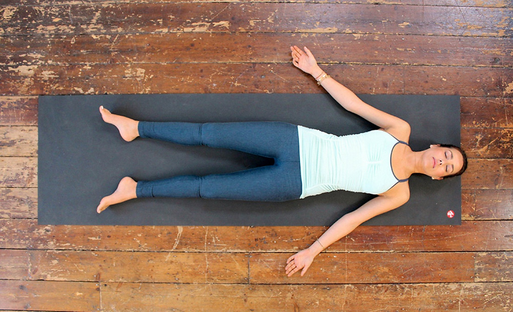 woman laying down in corpse pose relaxing