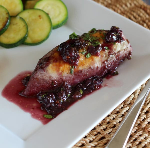 chicken breast with blueberry chipolte sauce and zucchini on a plate