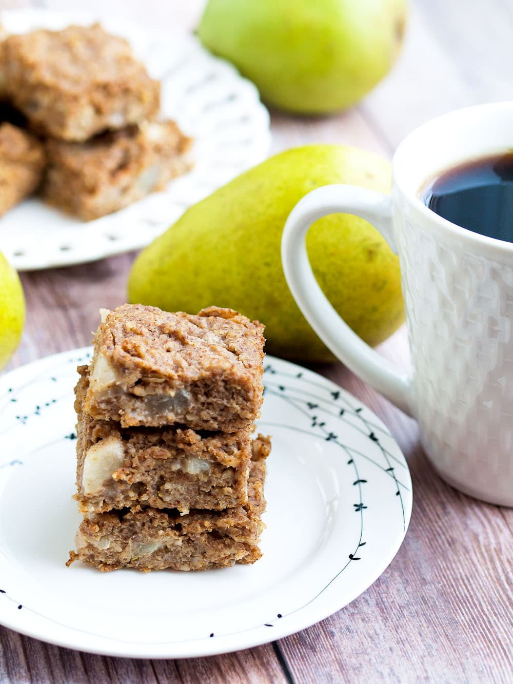 pear oatmeal bar on a plate with a cup of coffee