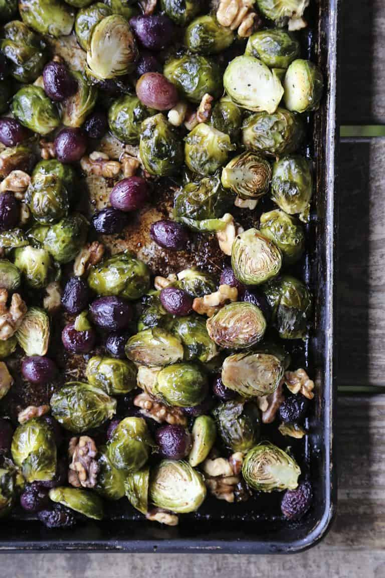 roasted brussels sprouts with grapes and walnuts on a sheet pan