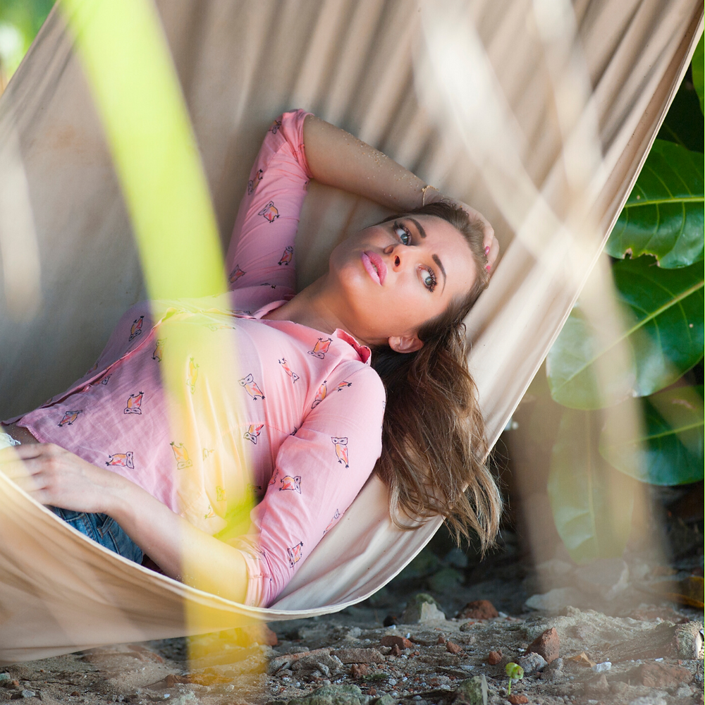 woman lying in hammock unsure of what she is going to do because she feels sick