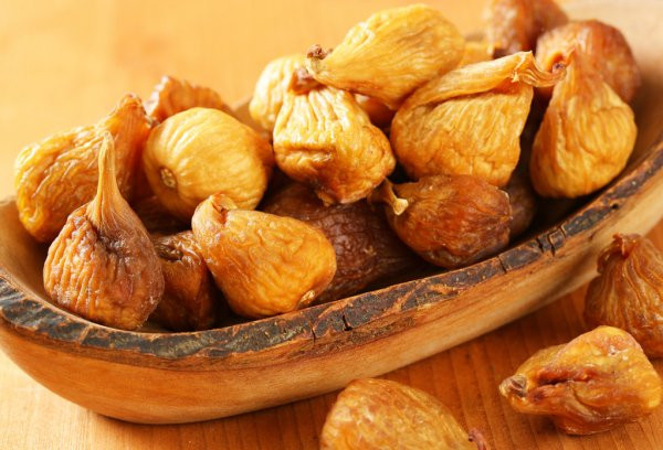 dried figs in a wooden bowl on a table