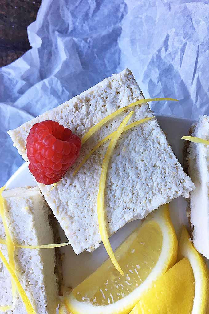 vegan lemon bar square surrounded by lemons and a plate
