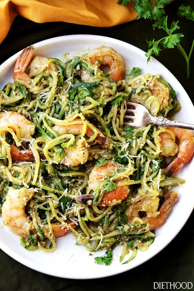 shrimp with zucchini noodles and pesto sauce on a dinner plate