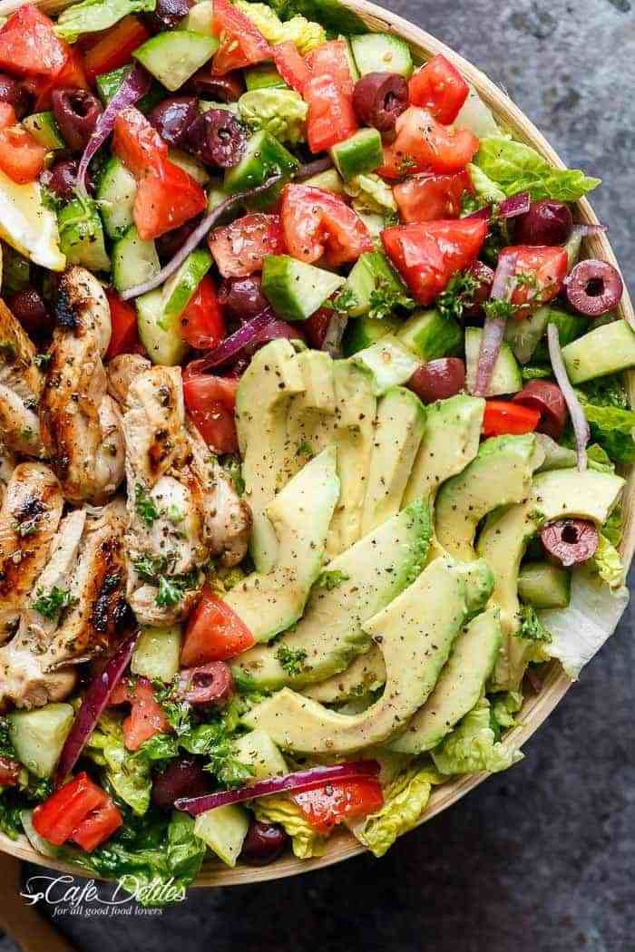 salad bowl with chicken, tomatoes, olives red onion and avocado
