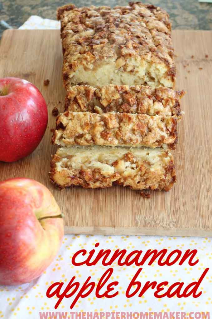 apple cinnamon bread on a wood cutting board with apples on the side