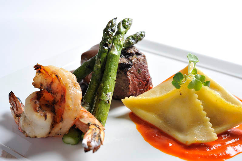 small plate of shrimp asparagus steak and ravioli