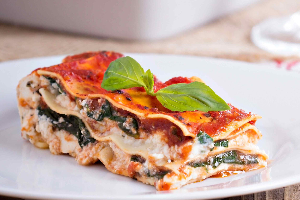 vegetarian lasagna on a plate topped with a basil leaf