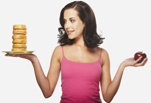 woman deciding between an apple and a stack of donuts