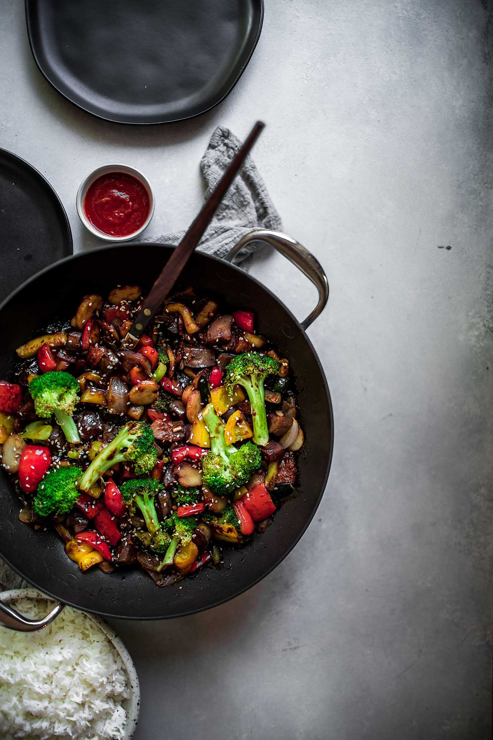 veggie stir-fry in a pan with sauce on the side